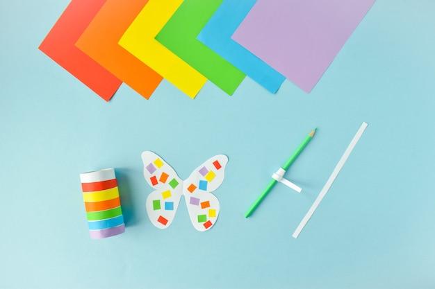 Een papieren vlinder gemaakt van gekleurd papier. lgbt-personages stapsgewijze instructies. stap 2. lijm en draai.