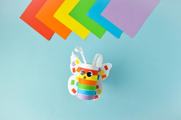 Een papieren vlinder gemaakt van gekleurd papier. stapsgewijze instructies voor lgbt-personages. stap 3. lijm en draai. de vlinder is klaar.