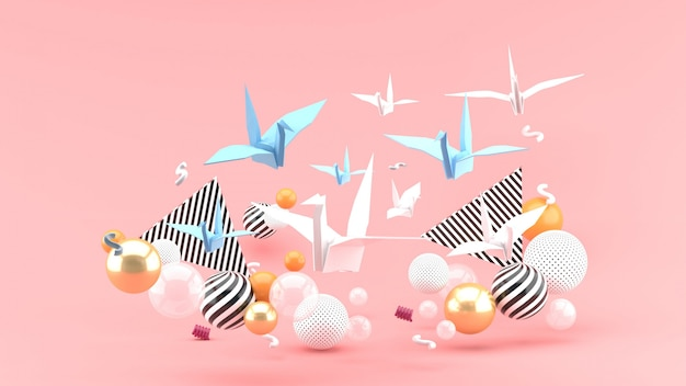 Een papieren vogel onder kleurrijke ballen op een roze ruimte