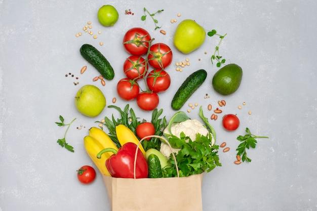 Een papieren zak vol met groenten en fruit close-up bovenaanzicht. gezond eten, winkelen concept, raw food dieet.