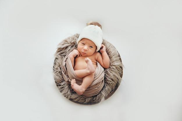 Een pasgeboren baby gewikkeld in een deken met een warme muts op zijn hoofd. de kindertijd, gezondheid, ivf.