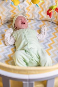 Een pasgeboren baby huilt in de wieg vanwege koliek