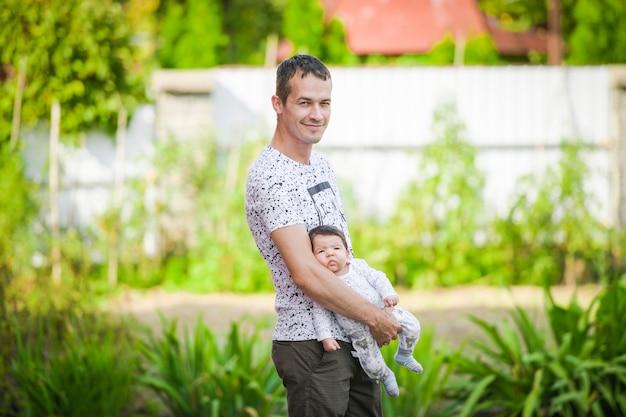 Een pasgeboren baby in de armen van zijn vader. een vader houdt zijn pasgeboren baby in zijn armen. blij vader