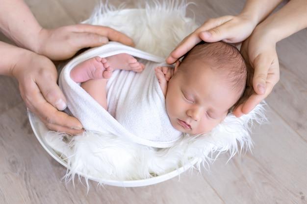 Een pasgeboren baby in de handen van ouders, een baby die slaapt in de handen van zijn vader en moeder