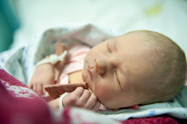Een pasgeboren baby op de eerste dag van zijn geboorte in de kraamkliniek