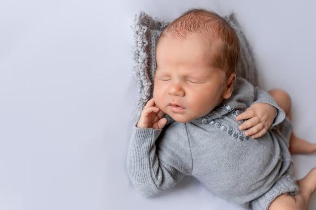 Een pasgeboren baby slaapt in een grijze bodysuit op een witte achtergrond met zijn hand onder zijn wang gevouwen