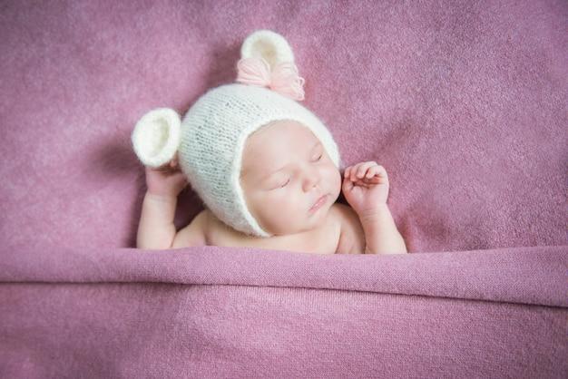 Een pasgeboren baby slaapt in een hoed met oren op een roze deken