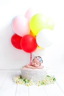 Een pasgeboren baby slaapt in een mandje met kleurrijke ballen.