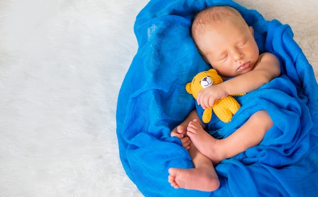 Een pasgeboren baby slaapt met een teddybeer. selectieve aandacht. mensen.