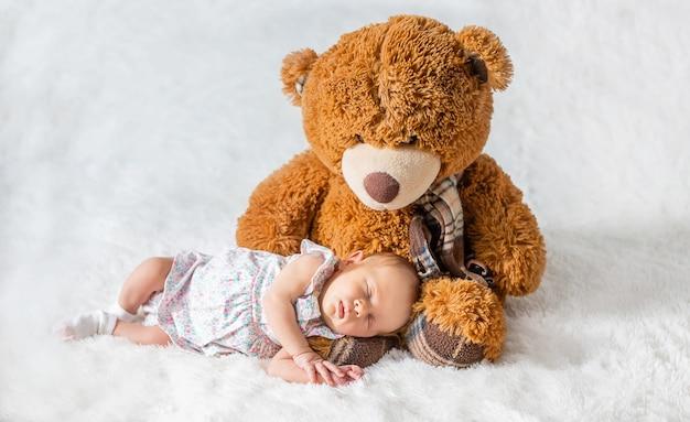Een pasgeboren baby slaapt met een teddybeer. selectieve aandacht.