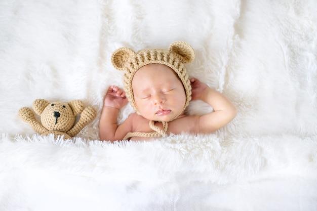 Een pasgeboren baby slaapt met een teddybeer