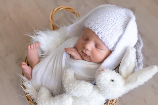 Een pasgeboren baby slaapt zoet in een luier-cocon in een hoed met hazenoren en met een zachte speelgoedhaas