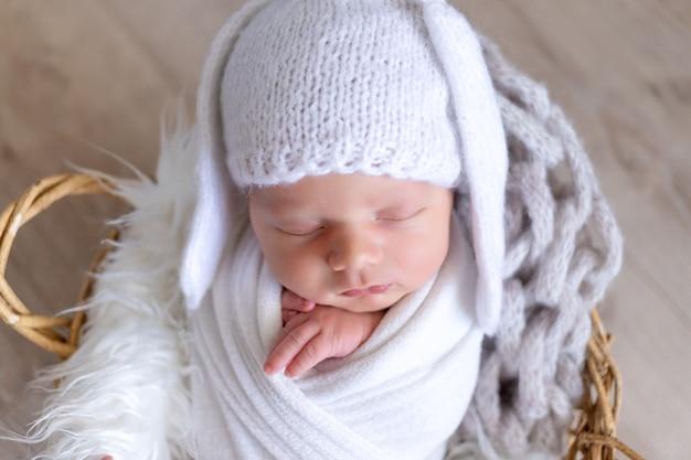 Een pasgeboren baby slaapt zoet in een luier-cocon in een hoed met hazenoren, portret
