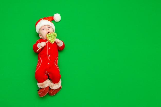 Een pasgeboren jongen in een rood kerstmanpak met bontlaarzen en een kerstmuts met een kerstpeperkoek in de zijne