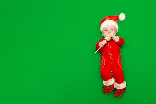 Een pasgeboren jongen in een rood kerstmanpak met bontlaarzen en een kerstmuts