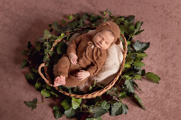 Een pasgeboren jongen slaapt in een mand in een beer outfit