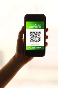 Een paspoort en een smartphone met een vaccinatiebewijs tegen de ziekte covid-19. focus op de slimme telefoon