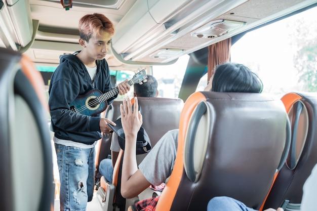 Een passagier weigerde met een handgebaar geld te geven aan een straatmuzikant die een ukelele droeg terwijl hij in de bus zat