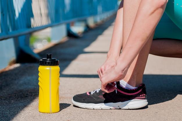 Een passieve en actieve vrouw die haar schoenen vastbandt voordat ze in een park joggen. runner met waterfles. fitness concept. hardlopen