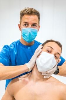 Een patiënt een nekmassage geven. fysiotherapie met beschermende maatregelen voor de coronavirus pandemie, covid-19. osteopathie, therapeutische chiromassage