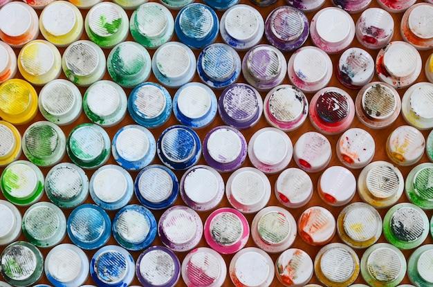 Een patroon van een groot aantal spuitmonden van een verfspuit voor het tekenen van graffiti, uitgesmeerd in verschillende kleuren.