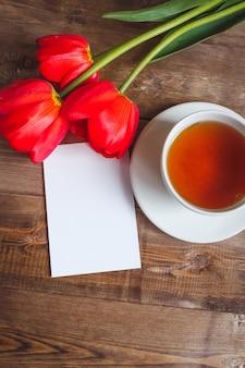 Een patroon van kop thee rood tulpen op houten lijst