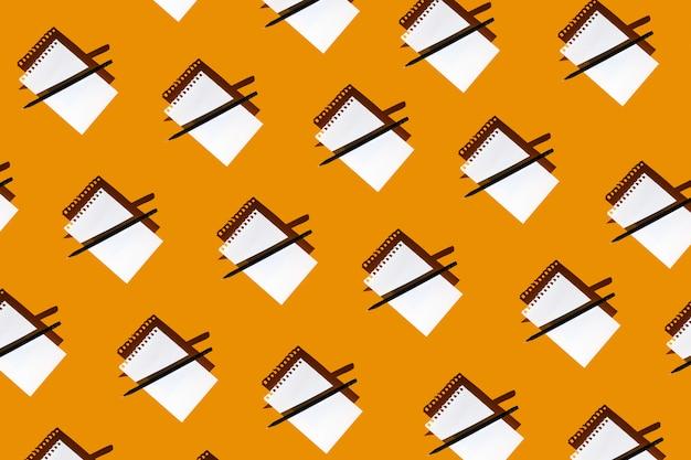 Een patroon van lege kladblok, zwart potlood en harde schaduwen op heldere gele achtergrond