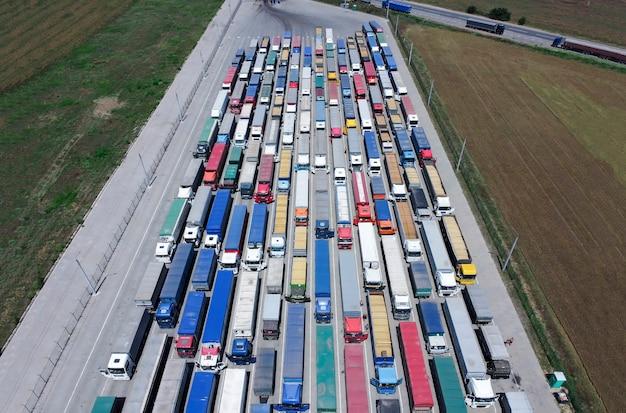 Een patroon van veel vrachtwagens die van een hoogte zijn gehaald. vrachtwagens stonden in de rij om graan te lossen in de haven.