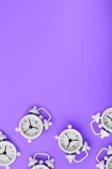Een patroon van veel witte klassieke wekkers in de vorm van een patroon op een paarse achtergrond. bovenaanzicht met een kopie van de ruimte, plat neergelegd.