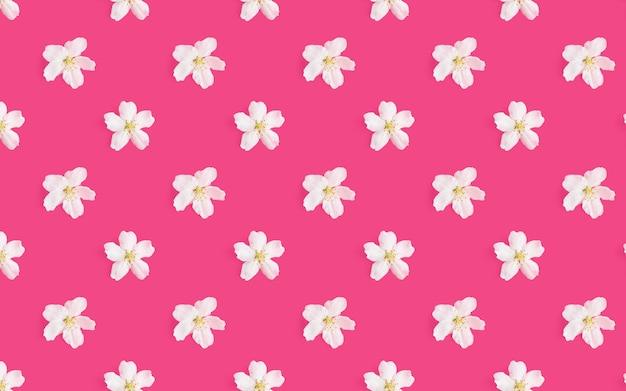 Een patroon van witte bloemen van een appelboom op een felroze achtergrond.