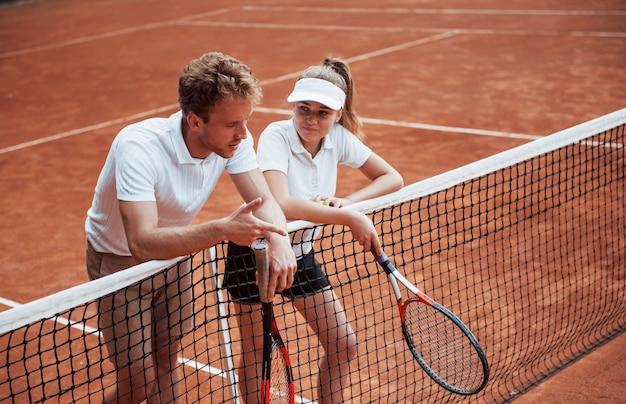 Een pauze nemen door op het net te leunen. twee mensen in sportuniform spelen samen tennis op het veld.