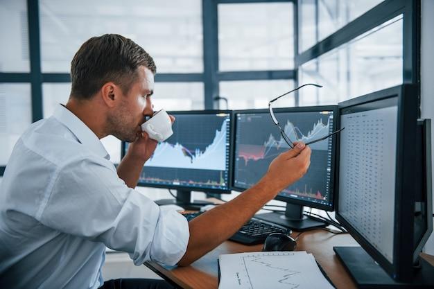 Een pauze nemen. houdt een kopje drank vast. jonge zakenman in formele kleding is op kantoor met meerdere schermen. conceptie van uitwisseling en geld.
