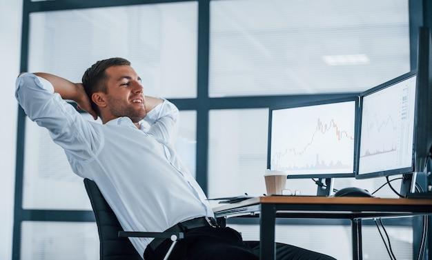 Een pauze nemen. jonge zakenman in formele kleding is op kantoor met meerdere schermen. conceptie van uitwisseling en geld.
