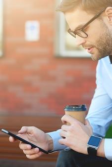 Een pauze nemen op het werk zijaanzicht van een knappe zakenman die smartphone gebruikt en koffie drinkt