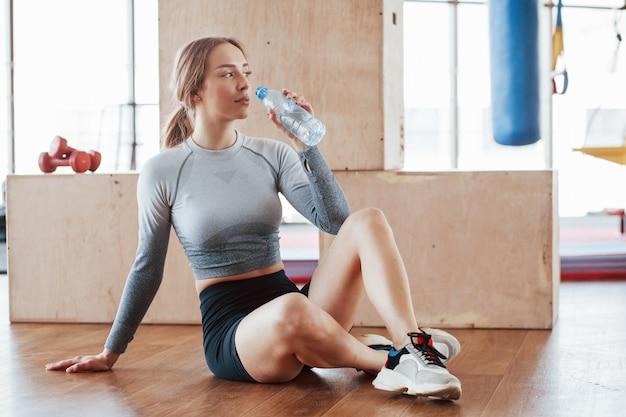 Een pauze nemen. sportieve jonge vrouw heeft fitnessdag in de sportschool in de ochtendtijd