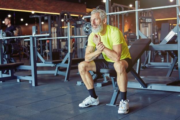 Een pauze nemen uitgeputte volwassen man in sportkleding die rust na een zware training in de sportschool