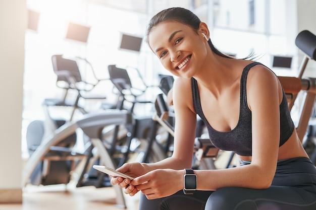 Een pauze nemen vrolijke en schattige jonge vrouw in sportkleding en koptelefoon met haar smartphone