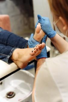 Een pedicure-meester doet een voetmassage en bereidt nagels voor op een pedicure