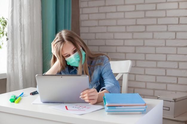 Een peinzend meisje in een medisch masker bestudeert thuis met een digitale tabletlaptop en doet huiswerk. afstandsonderwijs, online onderwijs