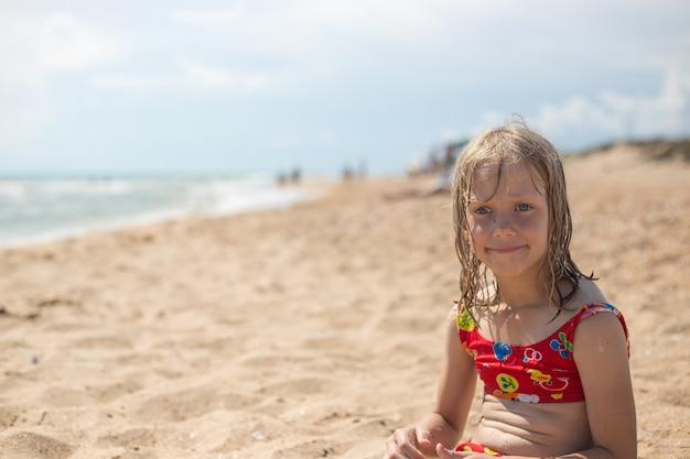 Een peinzend meisje met nat blond haar in een zwembroek zit aan de zanderige kust. zomervakantie, reizen en toerisme.