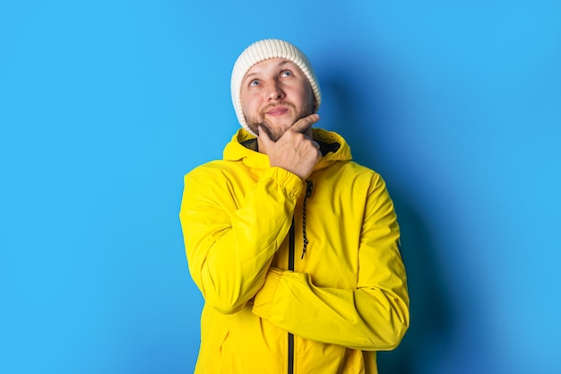 Een peinzende jongeman in een geel jasje kijkt op terwijl hij zijn hand onder zijn kin op een blauwe achtergrond houdt.