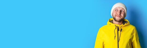 Een peinzende jongeman in een geel jasje kijkt opzij tegen een blauwe achtergrond. banier.
