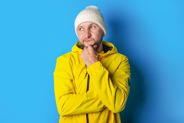 Een peinzende jongeman in een geel jasje kijkt opzij terwijl hij zijn hand onder zijn kin op een blauwe achtergrond houdt.
