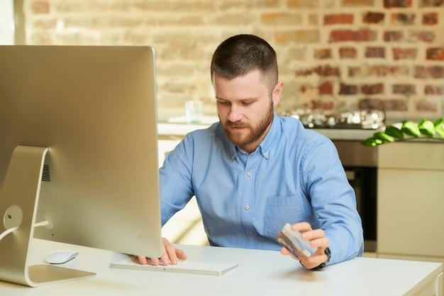 Een peinzende man met een baard typt creditcardgegevens om thuis online te winkelen