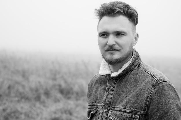 Een peinzende stijlvolle jongeman met een snor staat tegen grijze mistige natuur achtergrond