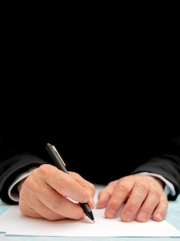Een pen in de hand van een man. wit vel papier. een document ondertekenen.
