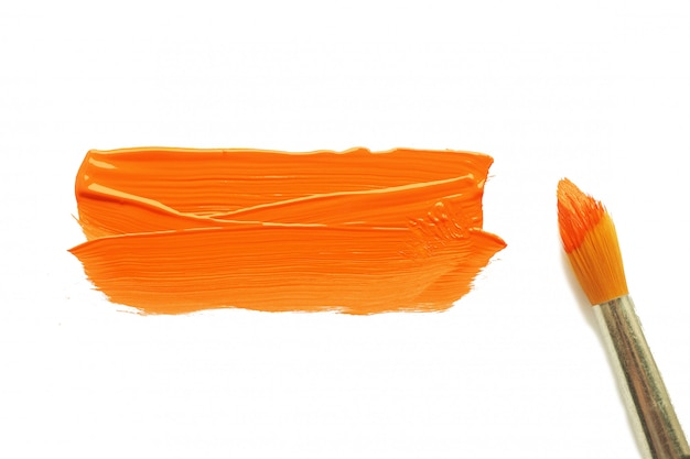 Een penseel in oranje verf en een vlekkerige oranje acrylverf op een wit blanco vel papier.