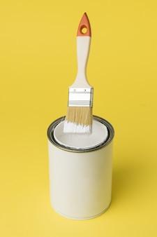 Een penseel vliegt over een open pot witte verf. uitvoering van schilderwerken.