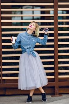 Een permanent blond meisje met roze lippen met een kopje koffie en luistert naar muziek op een smartphone met gestreepte houten balk achter