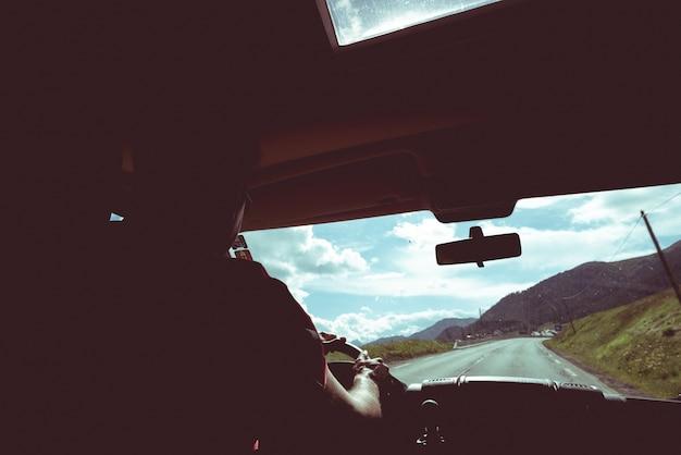 Een persoon campervan rijden in landweg, weergave van binnenuit, voorruit voertuig interieur, afgezwakt vintage